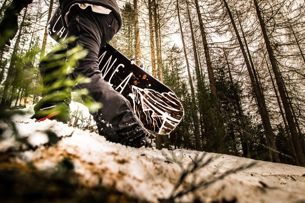 snowboarder con tavola caprabianca snowboard nel bosco