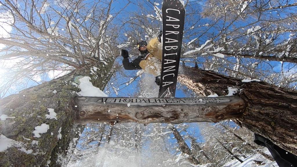 snowboarder che salta e fa trick con tavola caprabianca